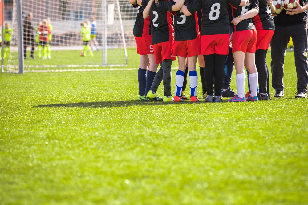Football Team on the Pitch. Girls in Black and Red Soccer Kits Standing Together on the Football Field. Motivated Young Soccer Players with Coach Talking Before the Final Game of School Tournament